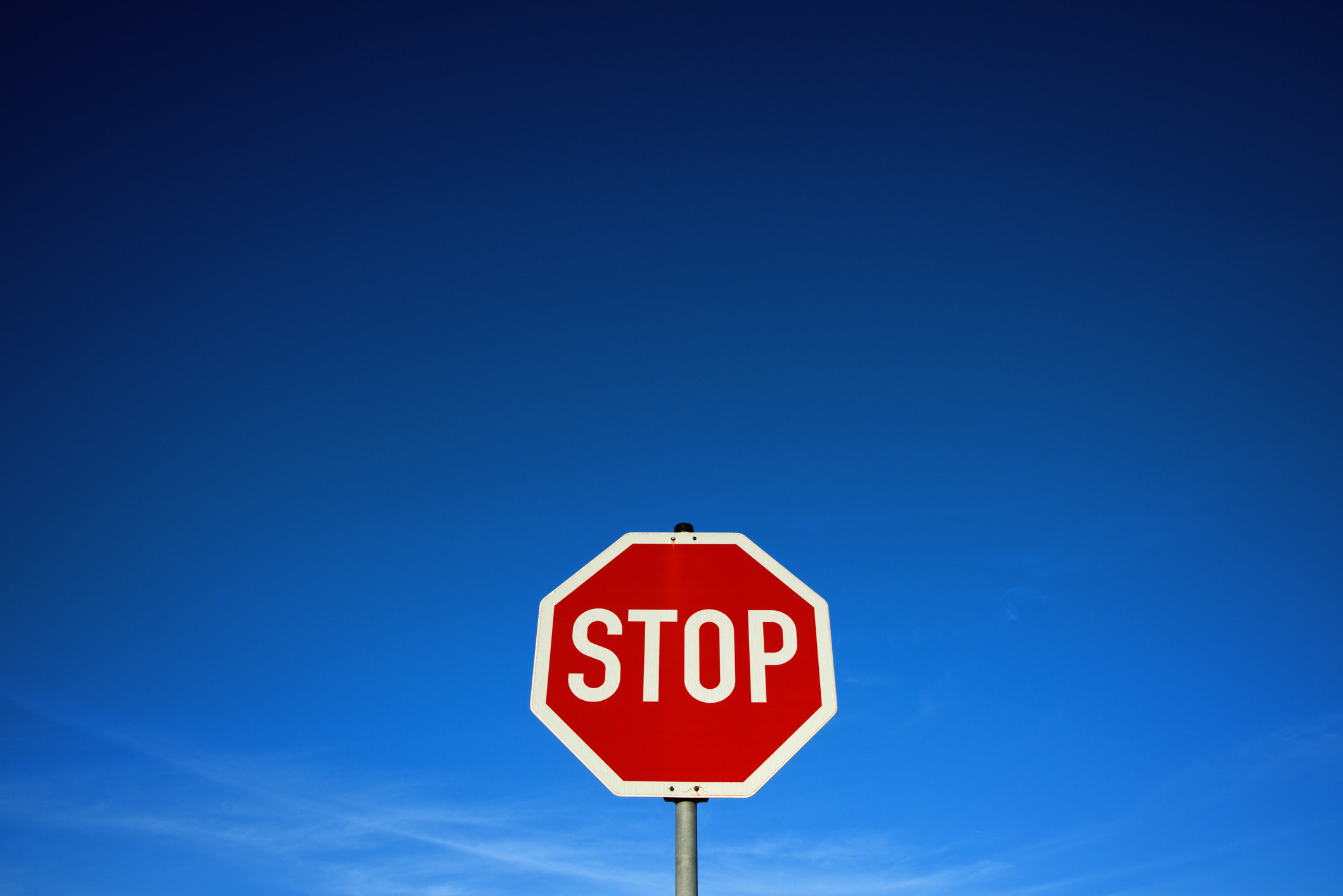 A stop sign at the bottom of the frame with a big empty sky behind it