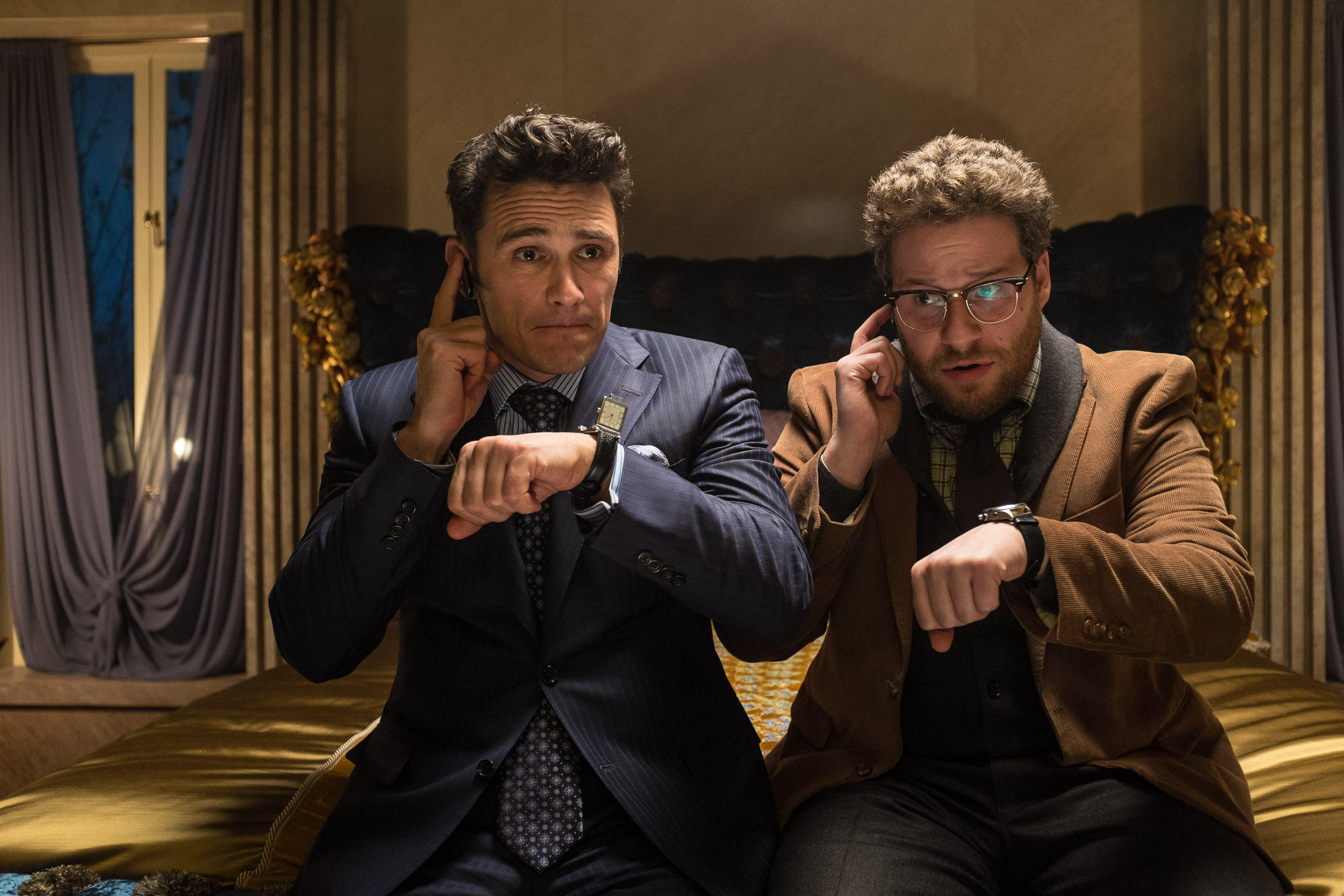 James Franco and Seth Rogen sit next to each other while touching their respective earpieces