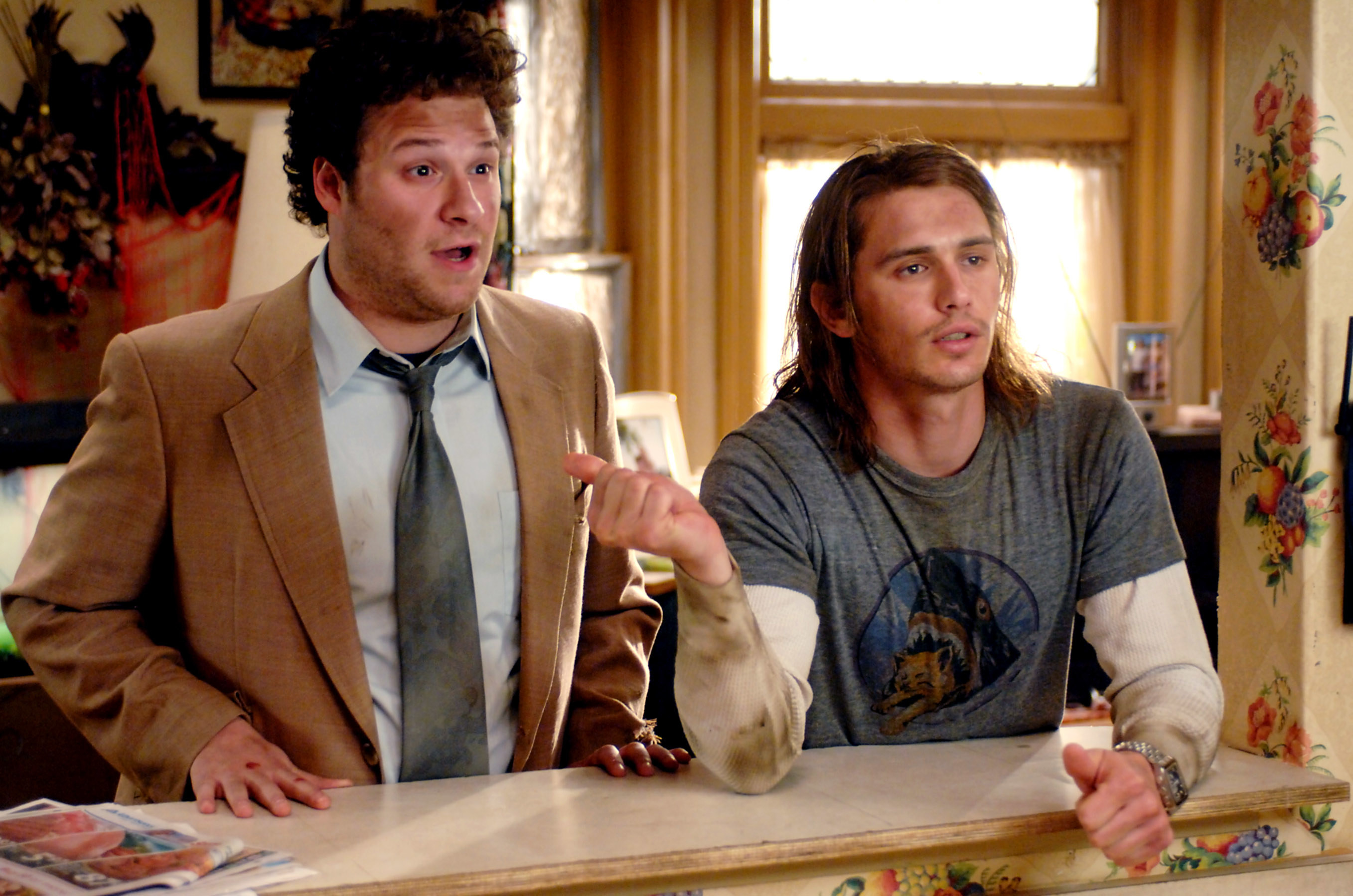 Seth Rogen and James Franco look disheveled as they lean on a counter