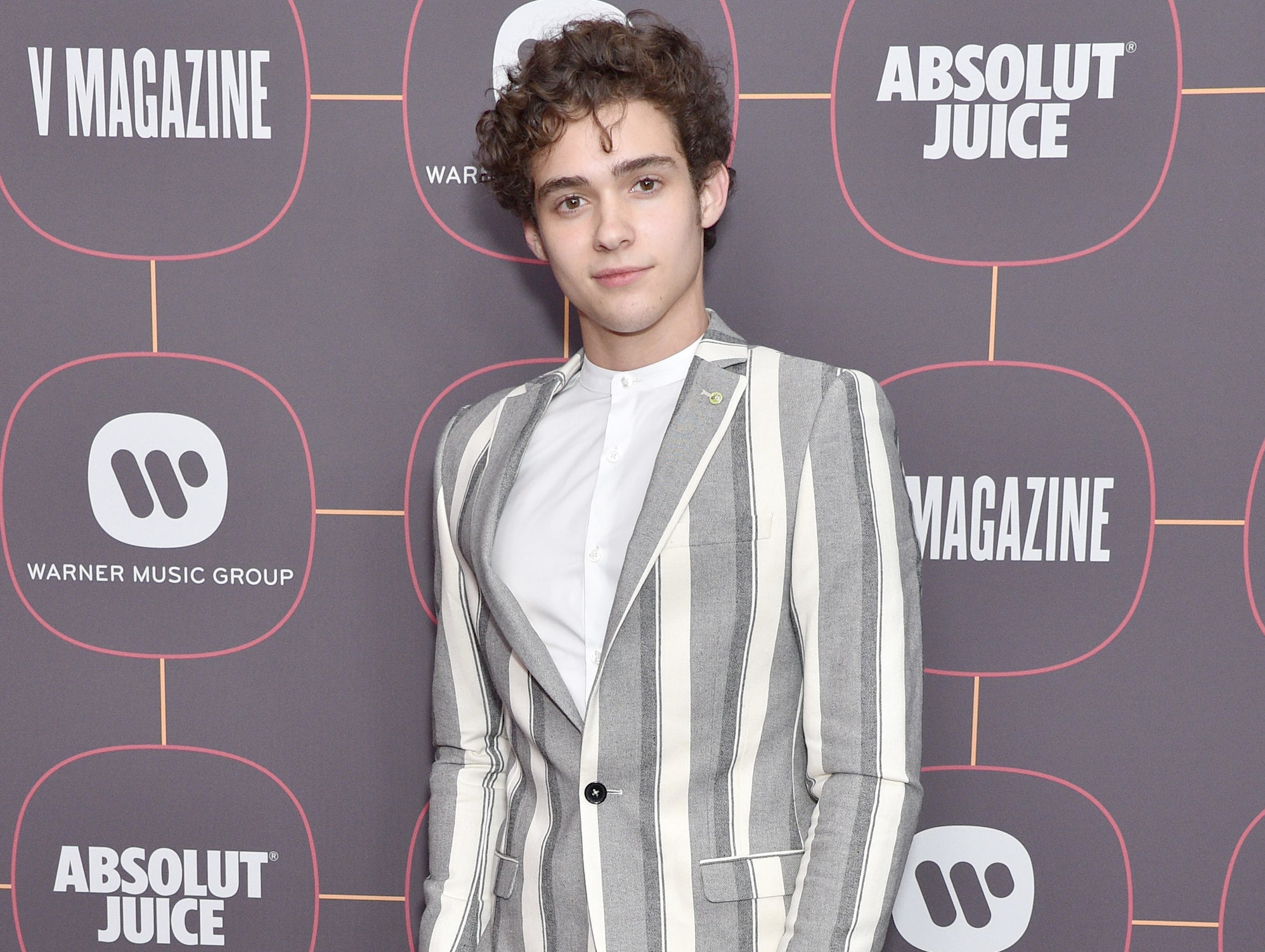 Joshua wears a striped blazer at an event