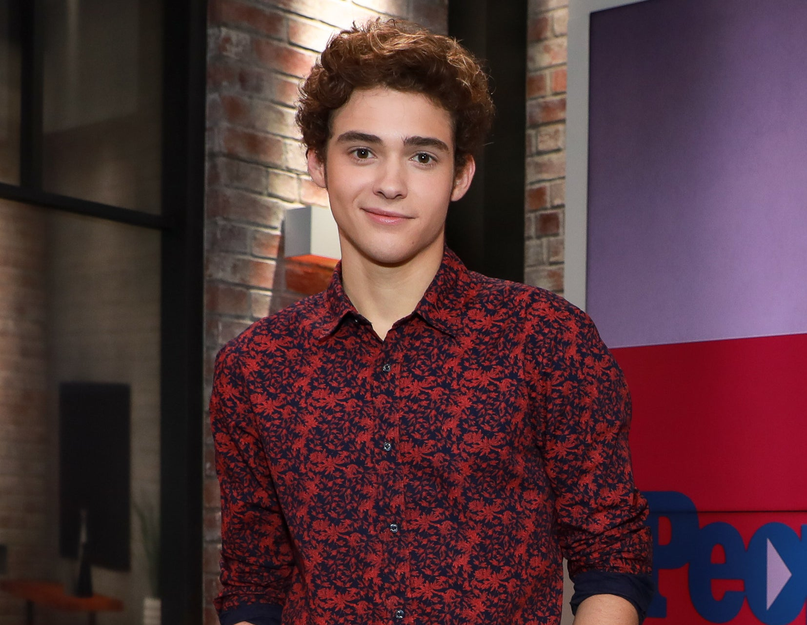 Joshua wears a red and blue floral patterned button down