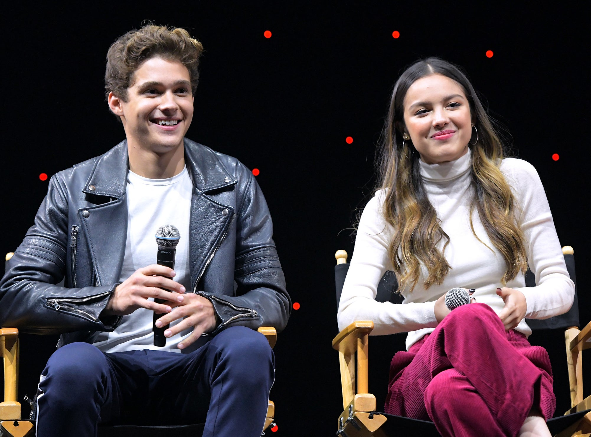 Joshua and Olivia smile while speaking onstage