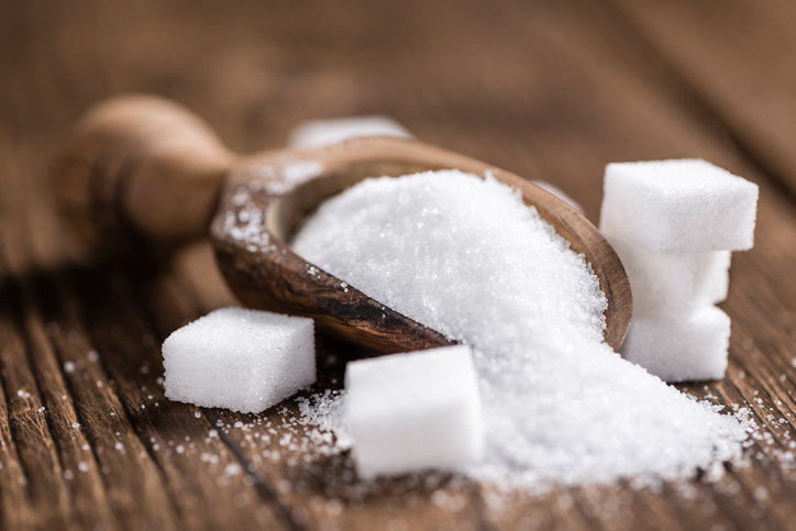 Wooden spoon filled with sugar and sugar cubes