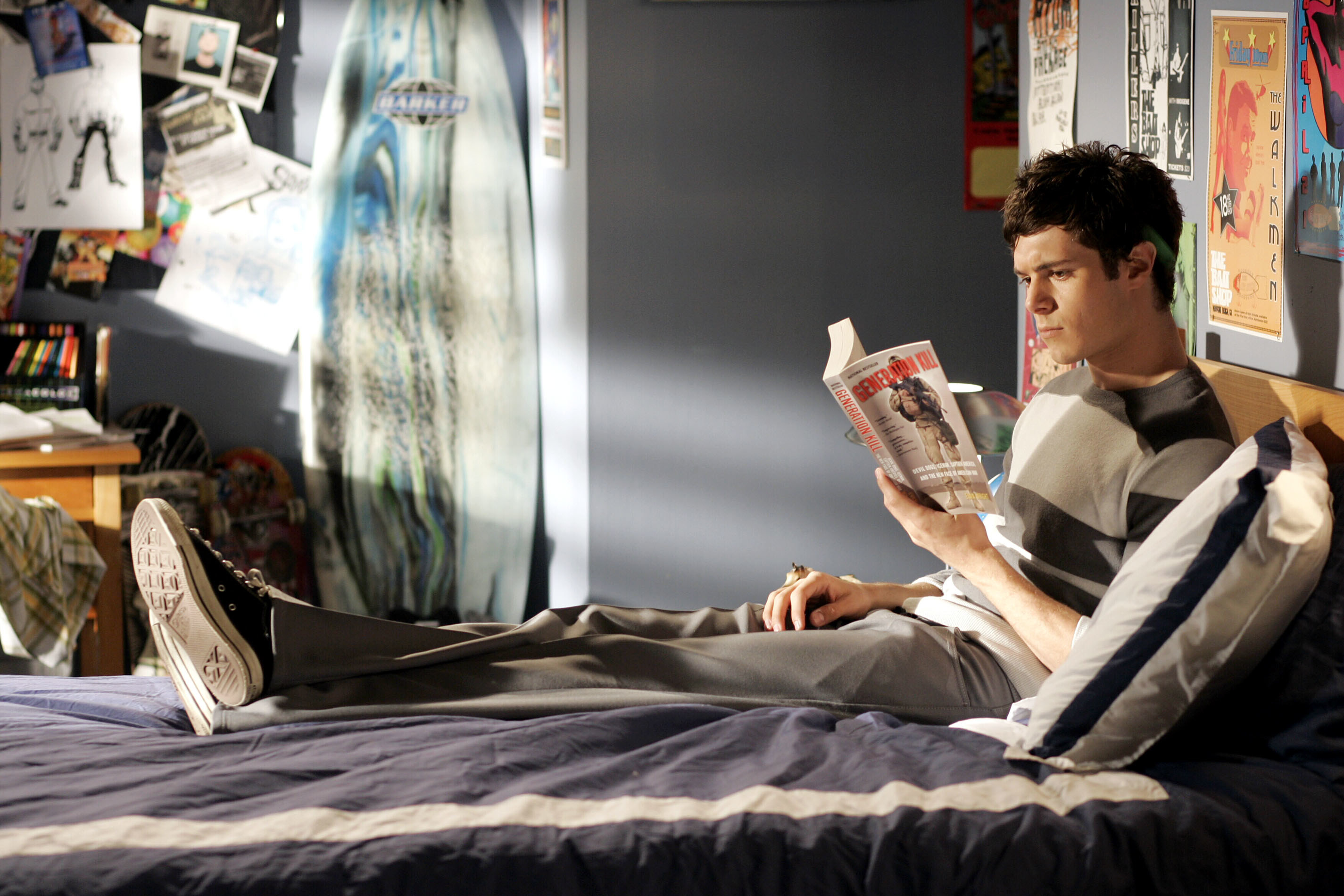 Brody sits on a bed while reading a graphic novel