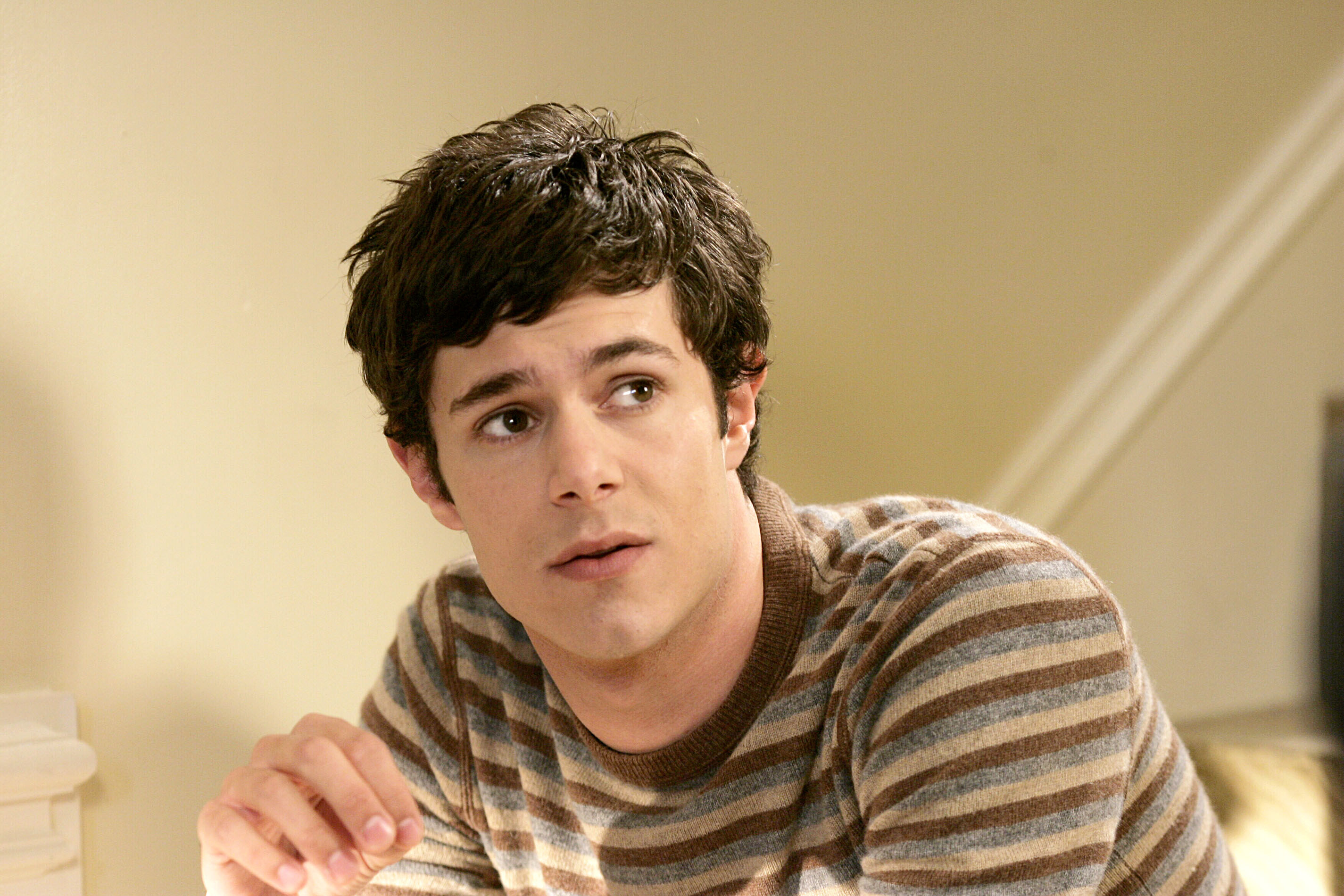 Adam Brody looks up while wearing a striped T-shirt