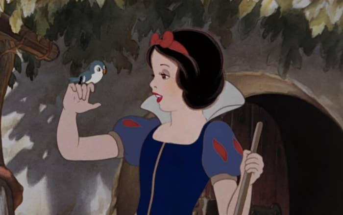 A bird perches on Snow White's finger
