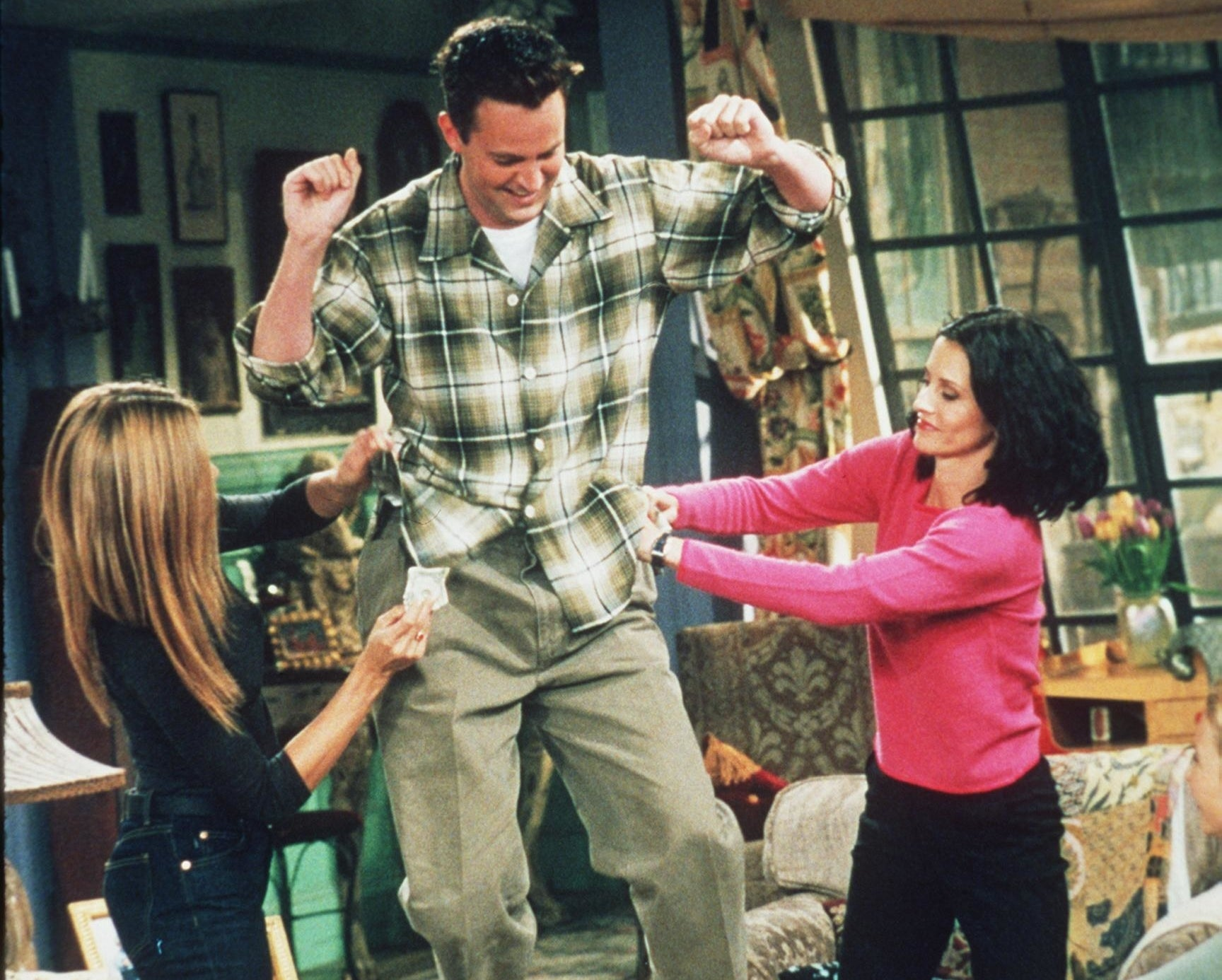 Jennifer andCourteney take money out of Matthew's pockets during a funny Friends moment