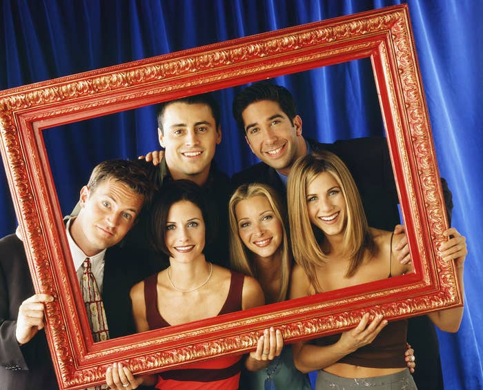 The whole cast poses while holding a red frame around themselves