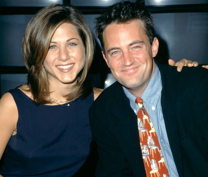 Jennifer and Matthew smile while posing during the '90s