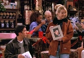 Phoebe showing off a framed picture of her dad which is actually just a stock photo model