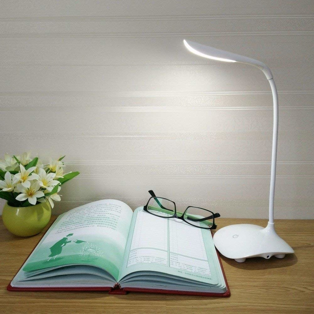 The lamp is kept on a desk with a notebook, spectacles, and plant.