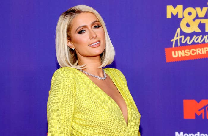 Paris Hilton smiles at camera in yellow dress while attending MTV TV & Movies Awards in 2021