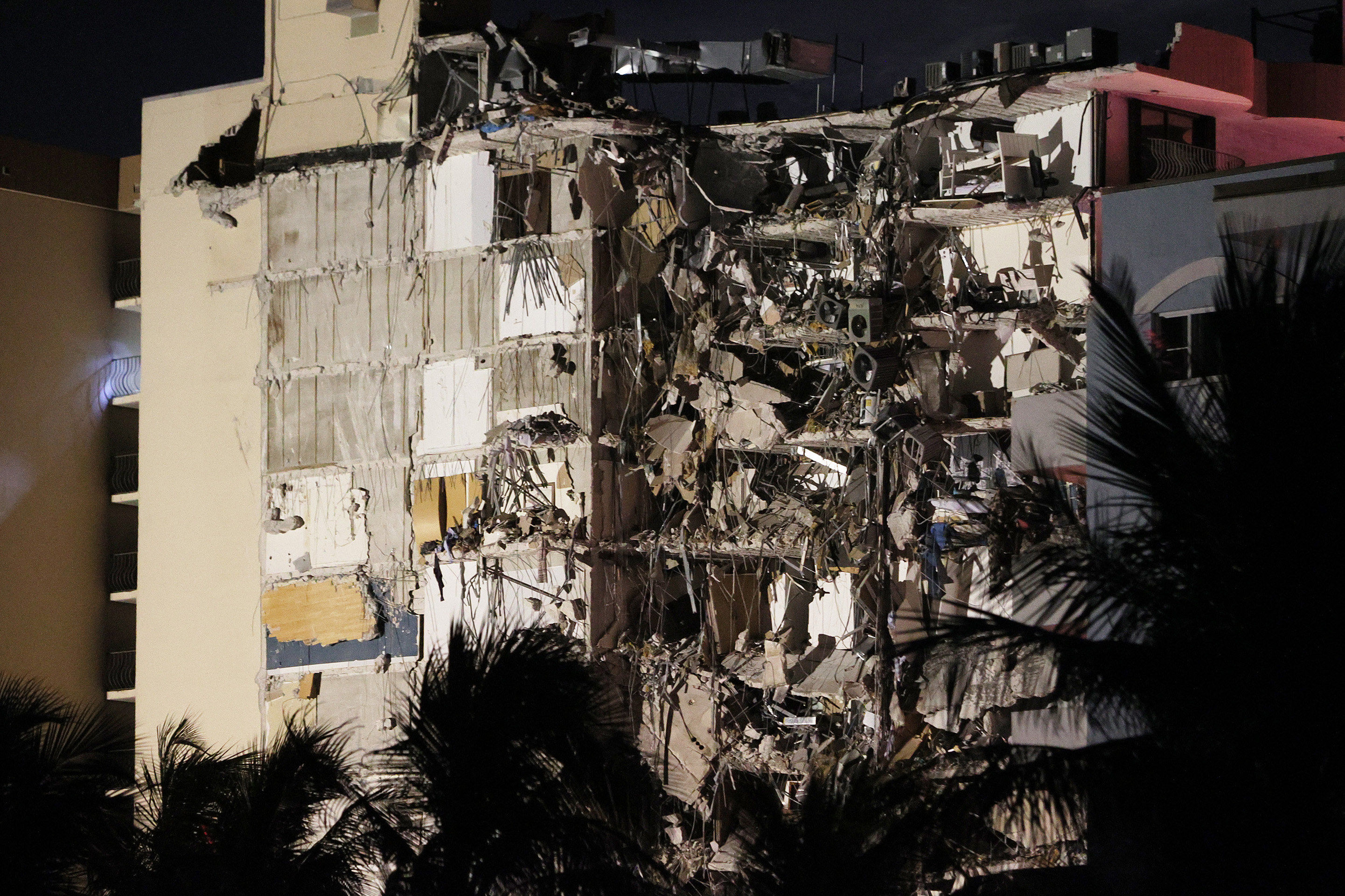 A side view of the partially collapsed building at night, with palm trees in the front