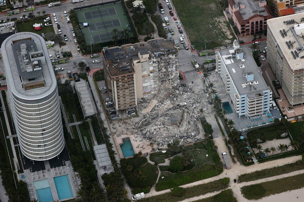 An overhead view of apartment buildings with one partially collapsed building in the center