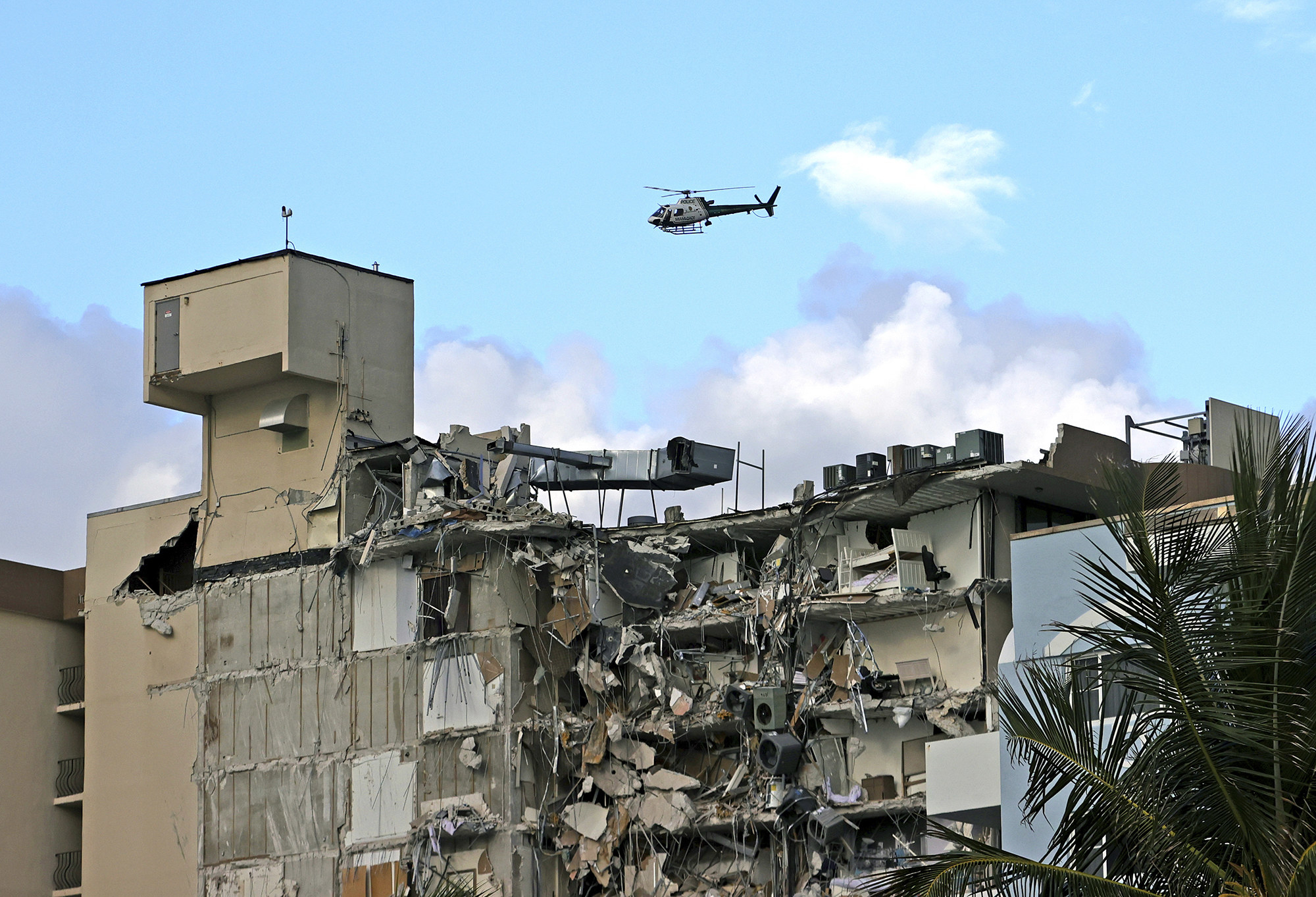 A helicopter flies over a partially collapsed building with a palm tree in the foreground