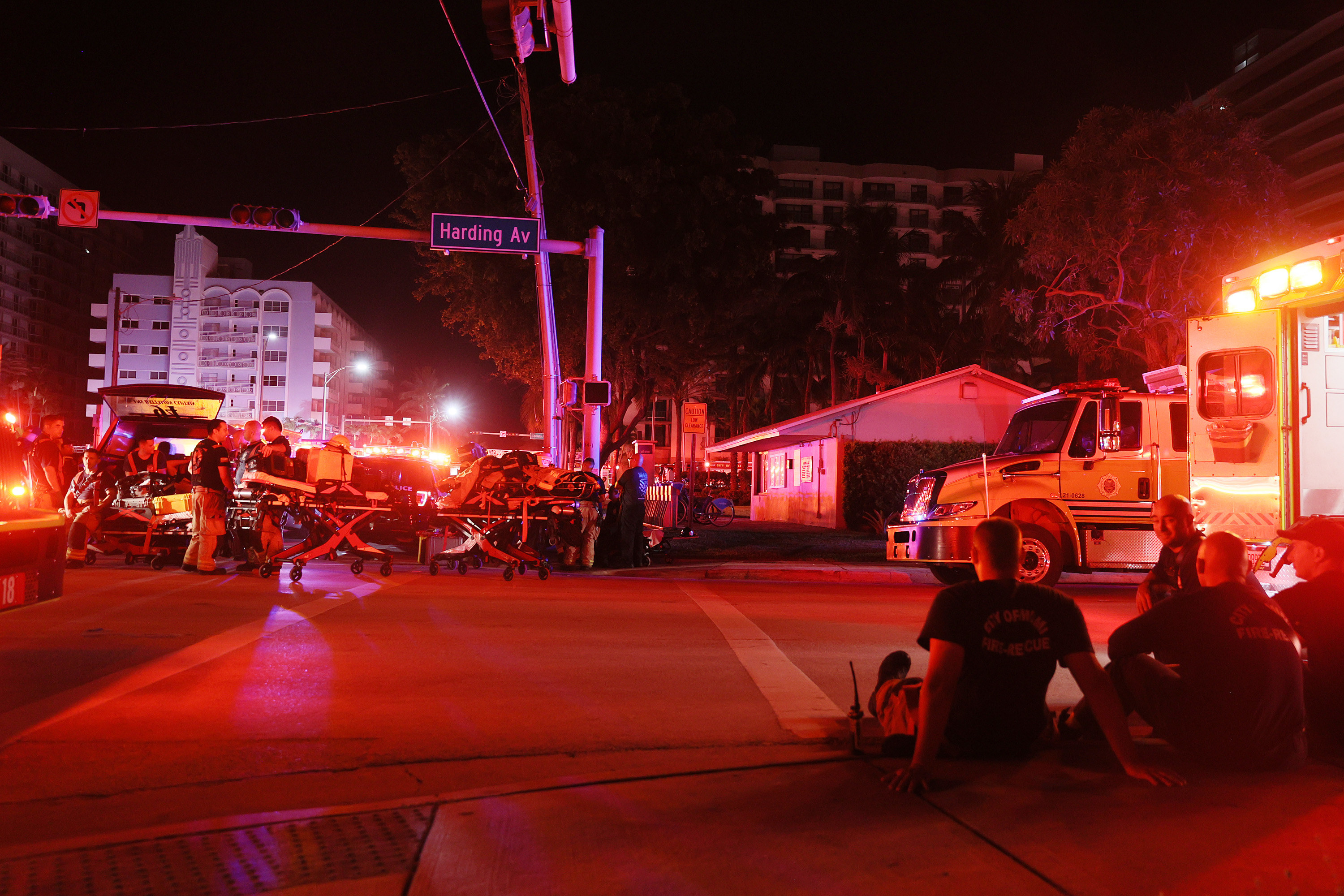 Rescue personnel sit on the sidewalk surrounded by emergency vehicles with red lights flashing