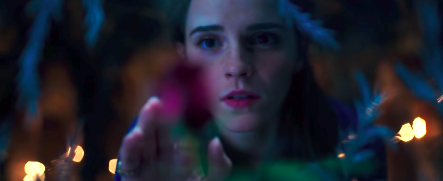 Belle in the live-action remake looking at the flower