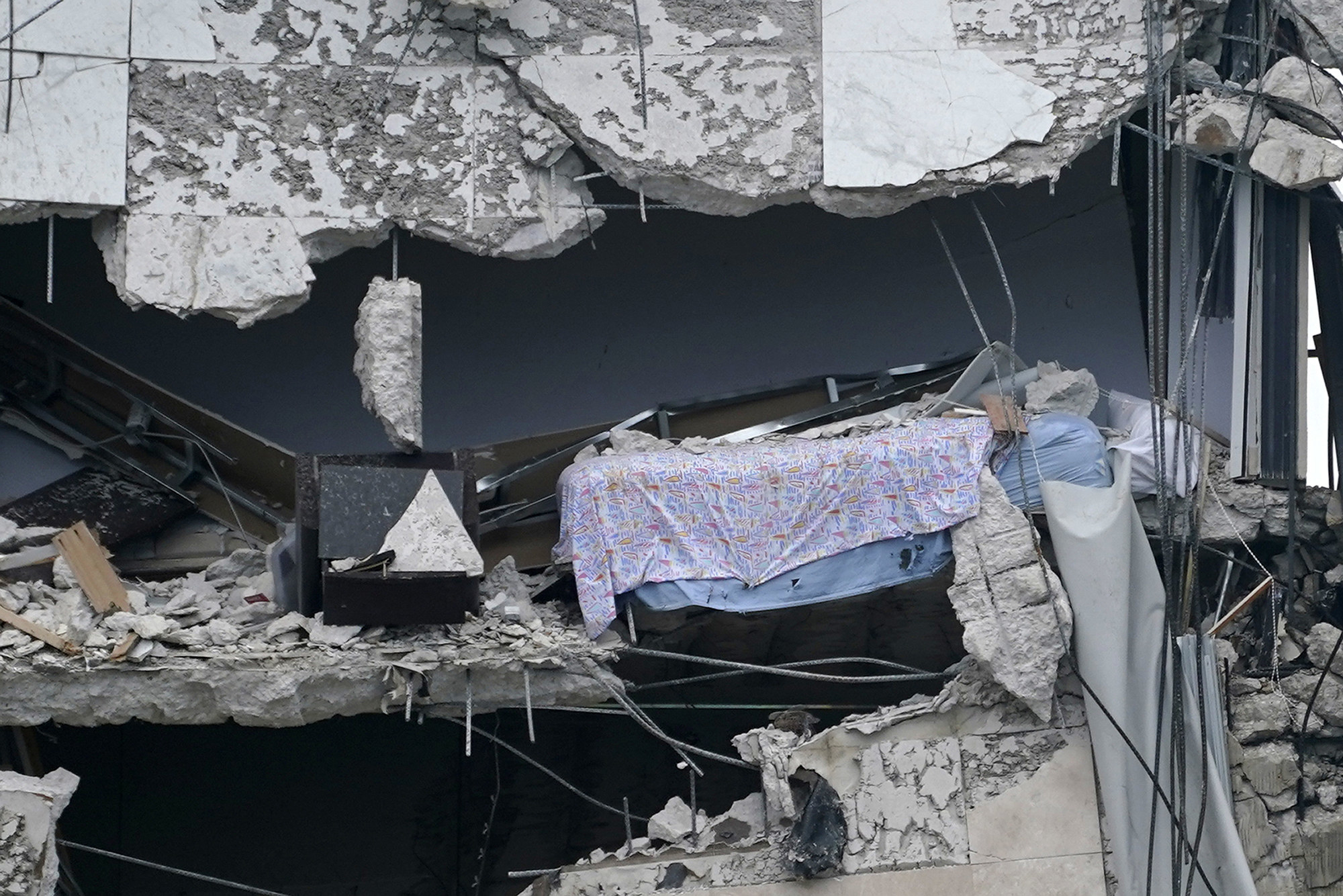 A bedroom with pink sheets is visible as the walls fell away at a partially collapsed building
