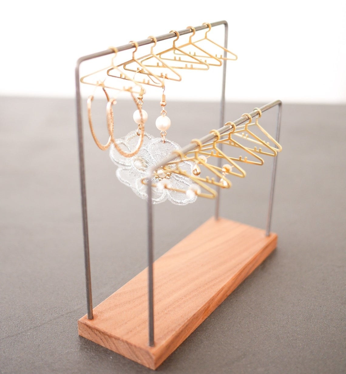 two bars with small gold hangers and earrings hanging from them