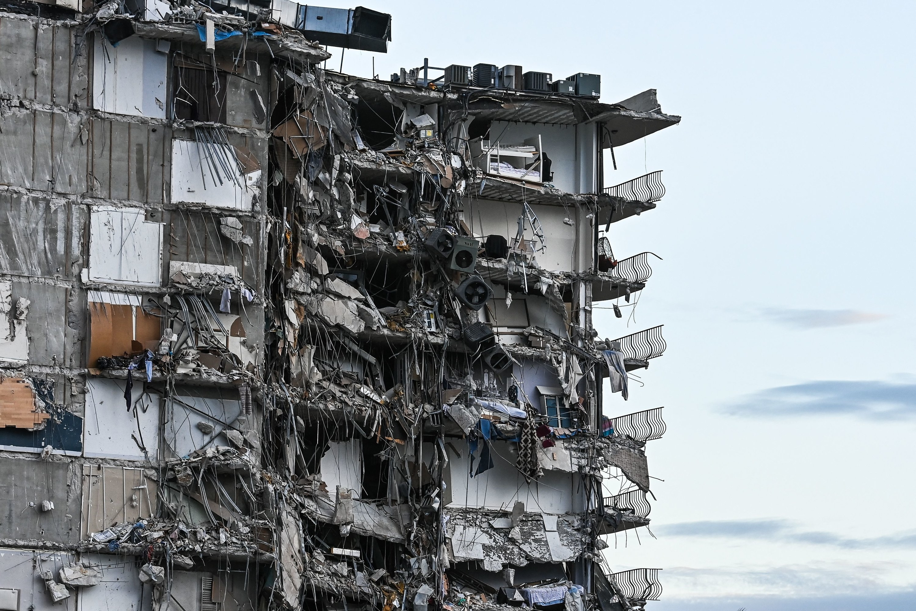 Six stories of a partially collapsed building with the inside visible and balconies hanging off the side