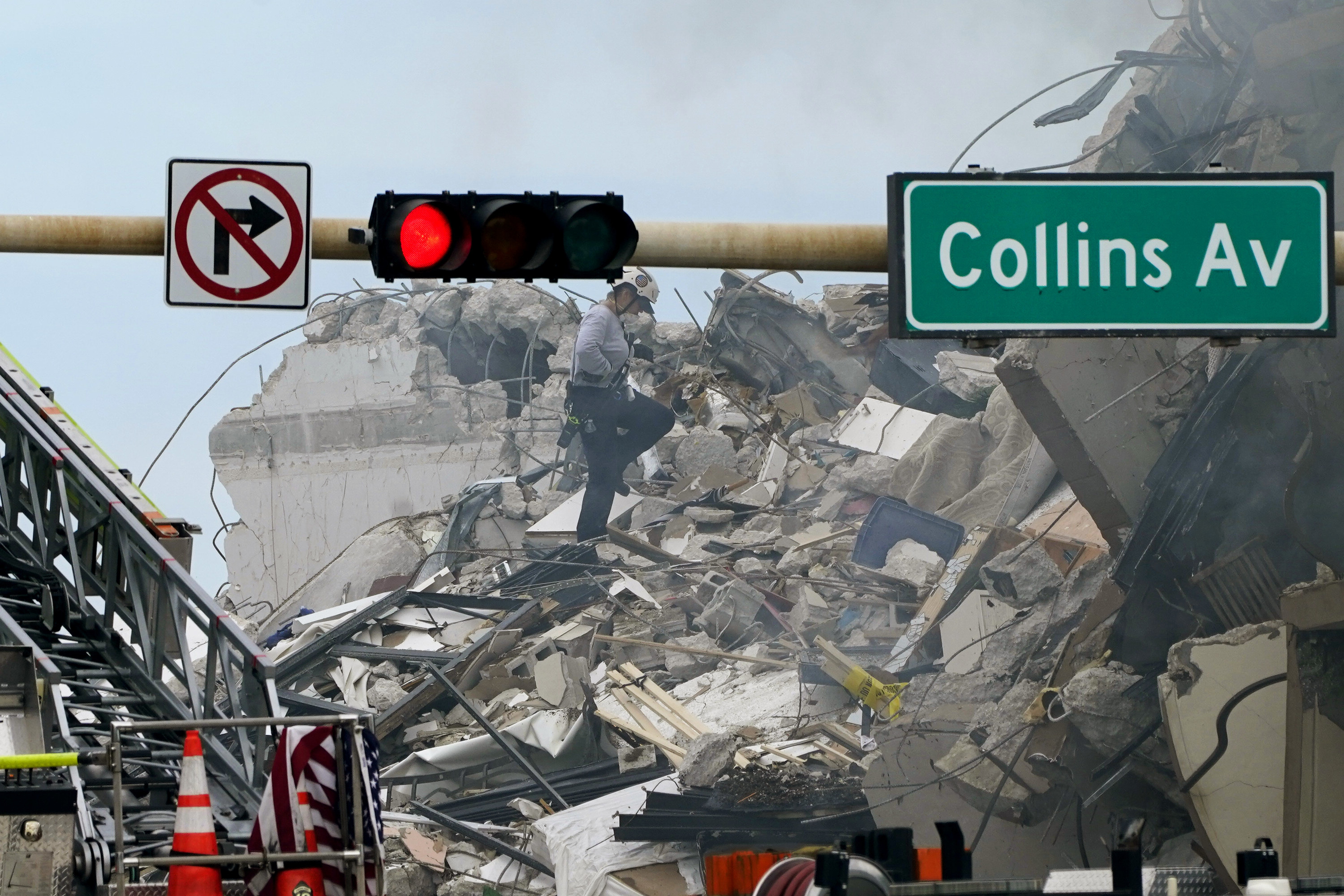 A rescue worker walks on the rubble of a partially collapsed building, with a Collins Ave sign and stoplight in the foreground