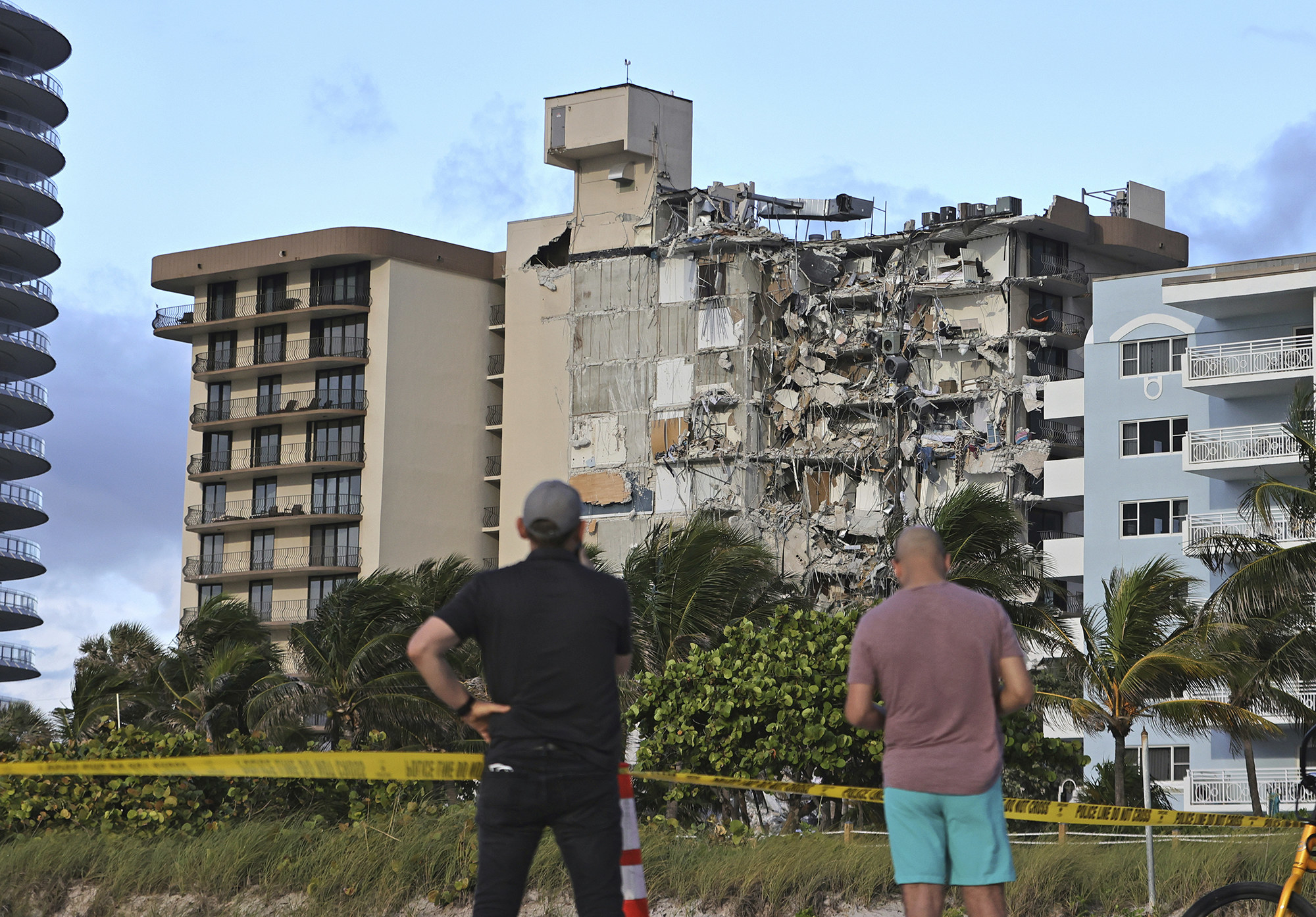 Two men from behind look at a partially collapsed building from behind caution tape