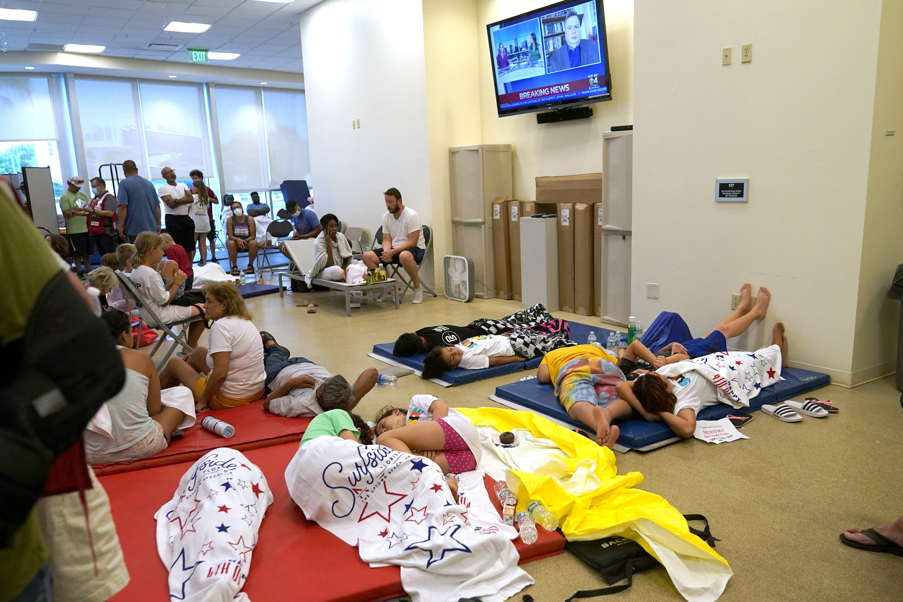 People lie on gym mats under towels in a beige room with a television on the wall playing breaking news