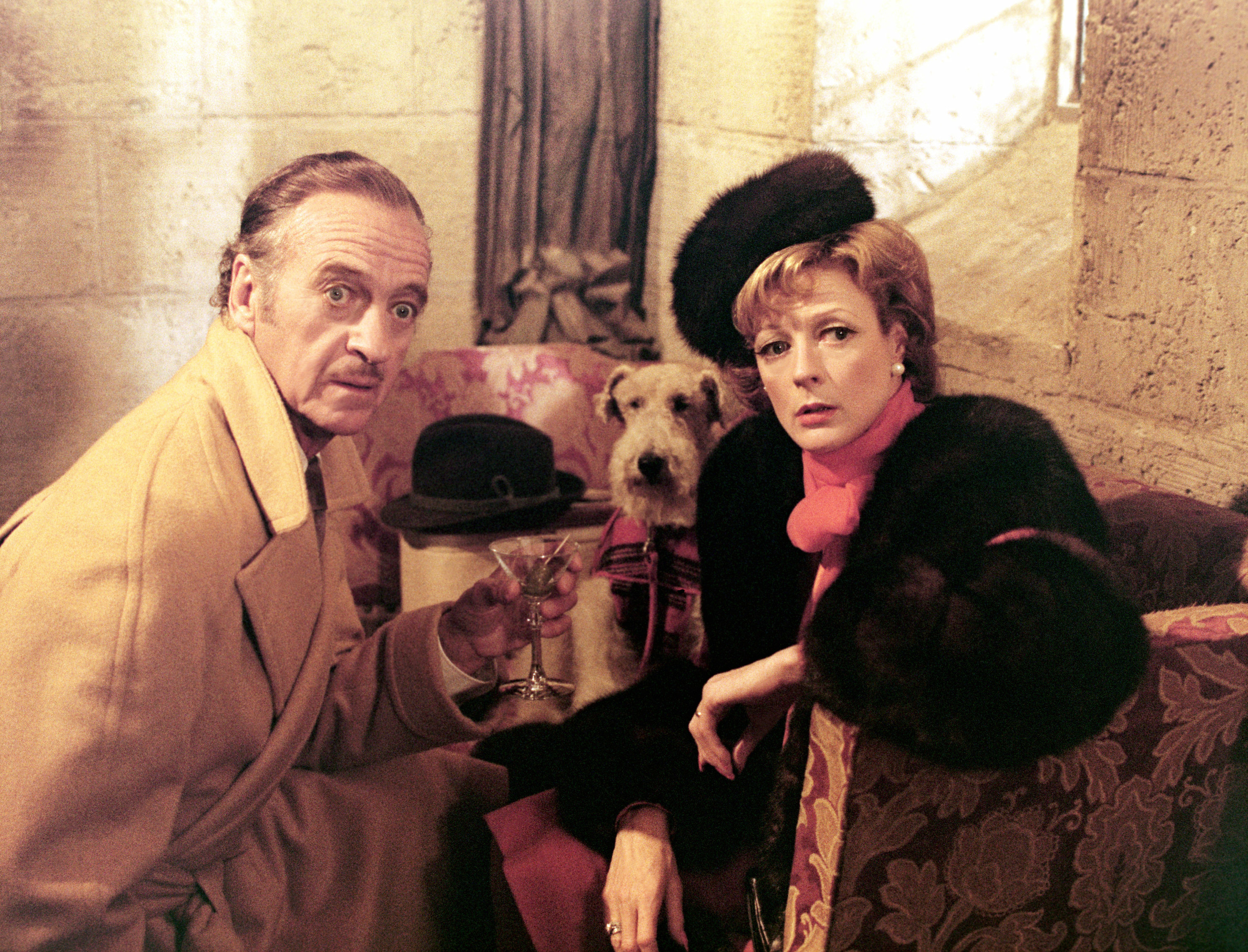David Niven, Maggie Smith, and a dog sitting on a couch