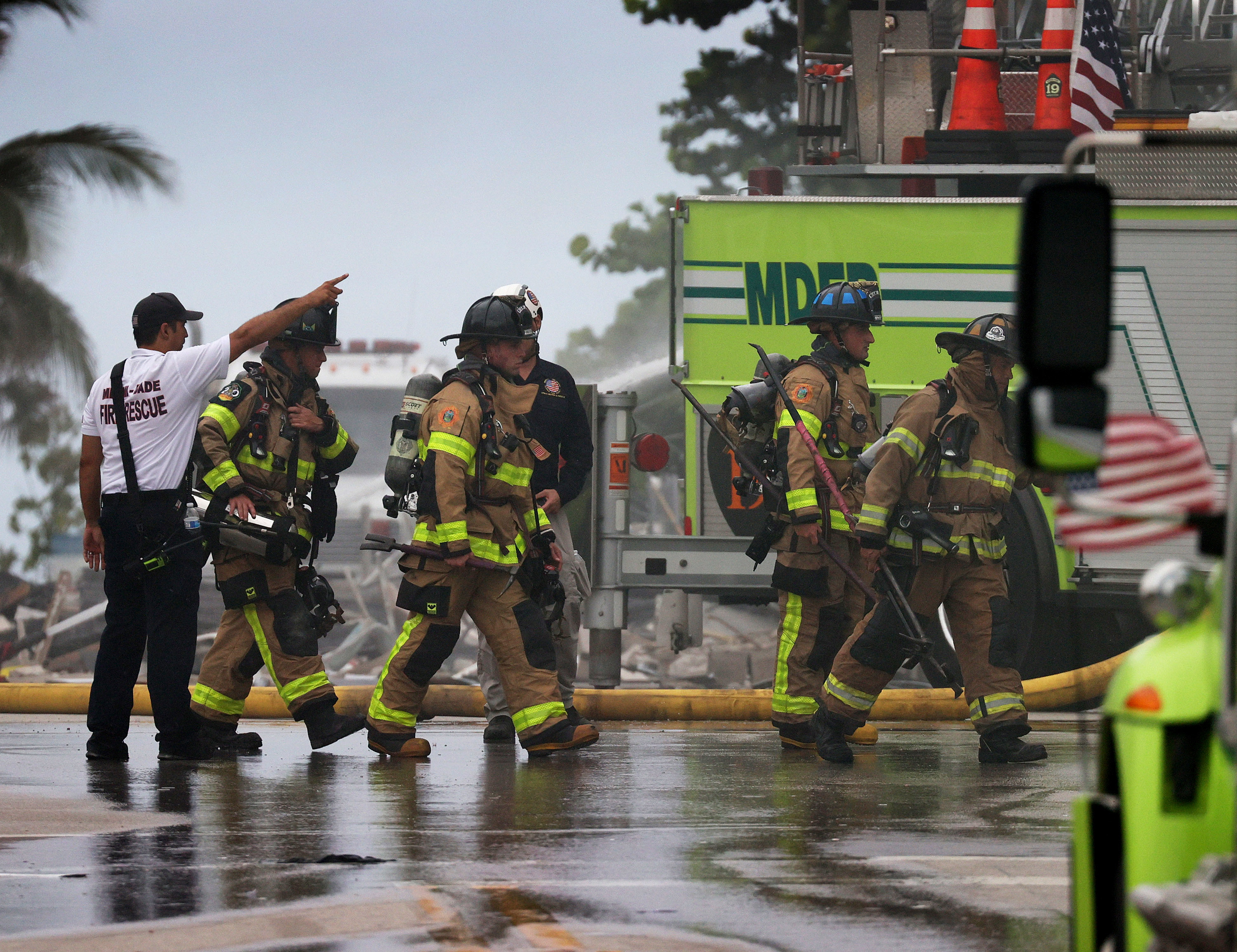 Firefighters walk on wet ground toward the partially collapsed building as a rescue worker points