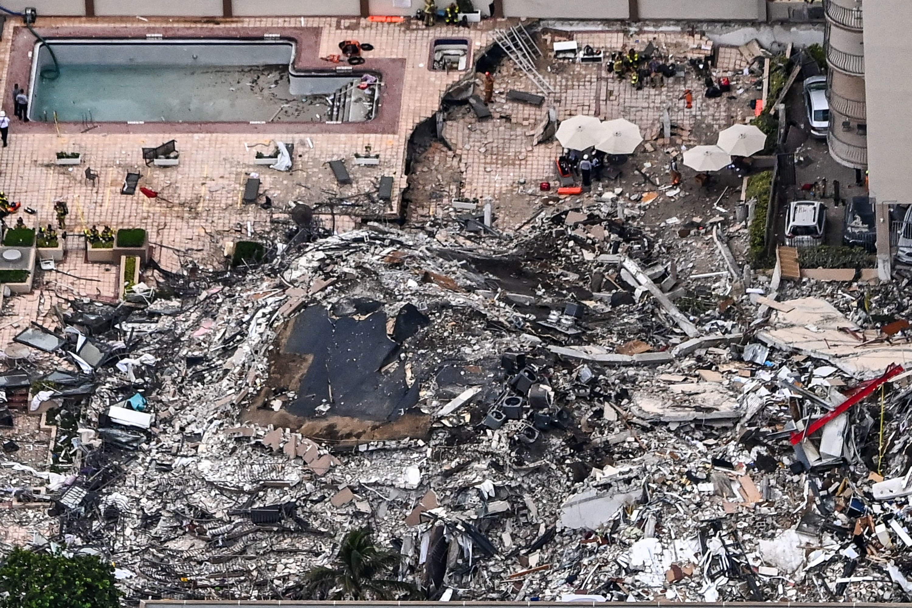 An overhead view of rubble from the partially collapsed building, an emptied pool, and umbrellas