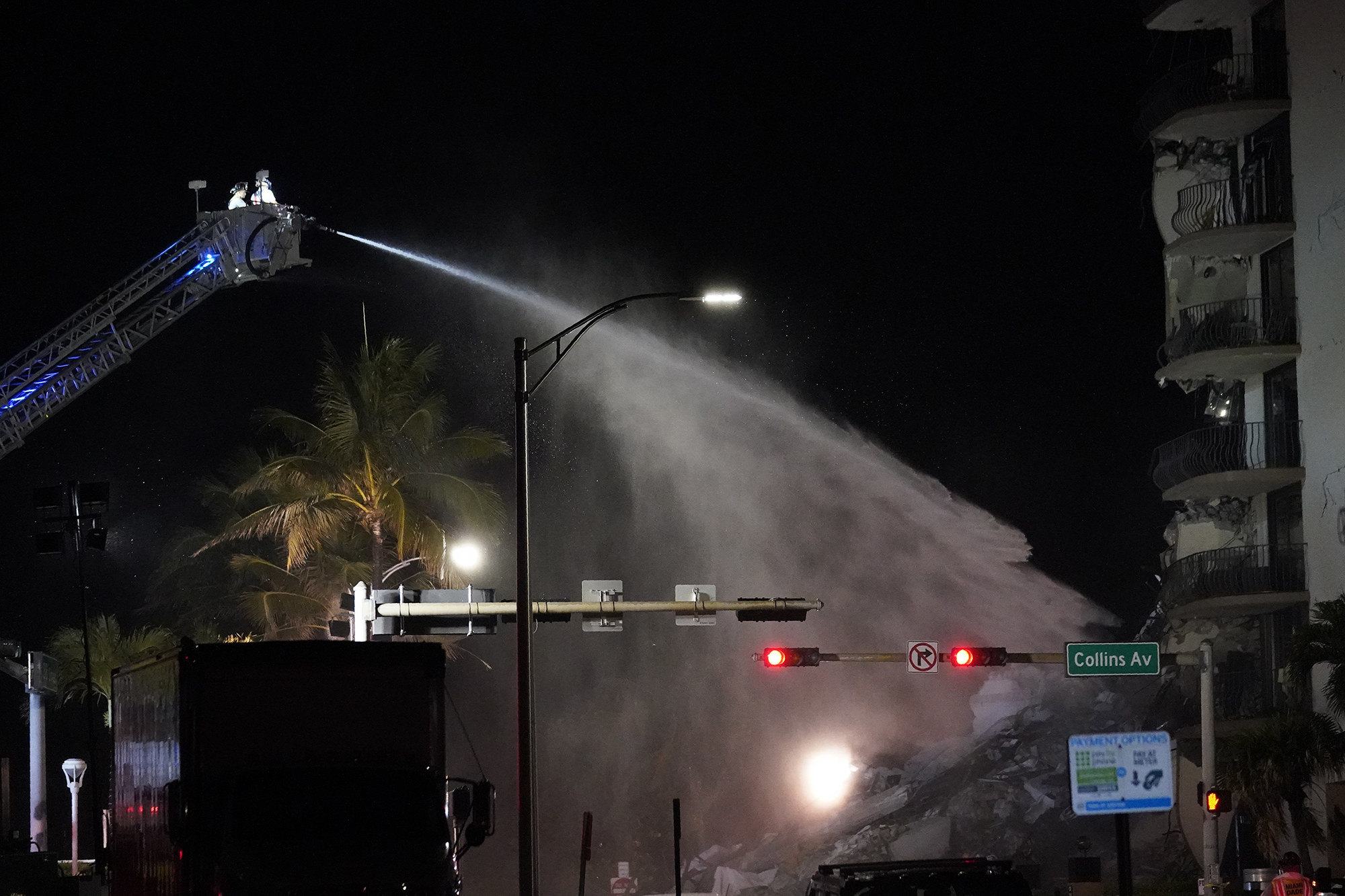 A fire ladder sprays water onto the rubble of a partially collapsed building at night