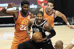 Paul George of the LA Clippers holds a basketball, surrounded by Phoenix Suns players