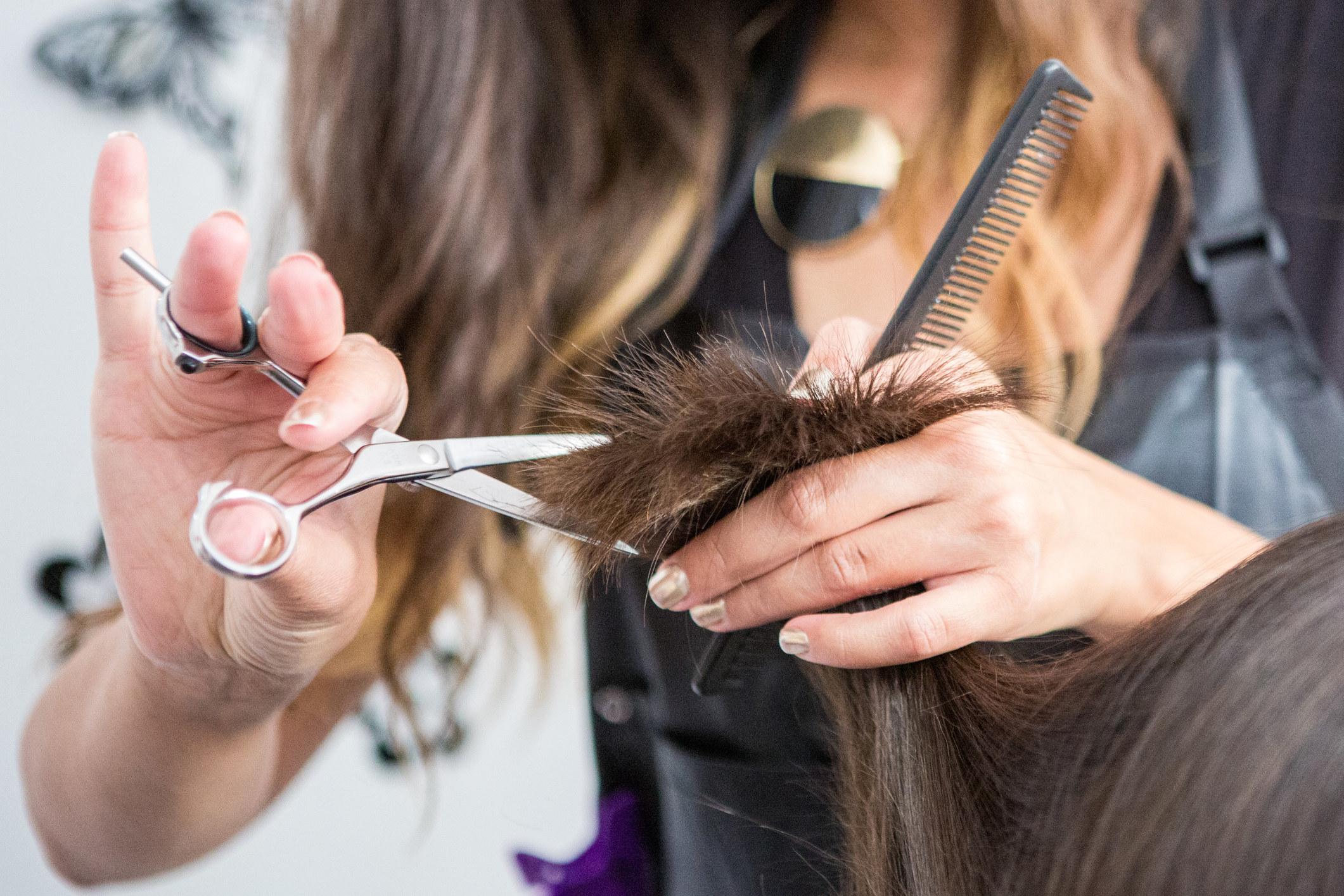 A hairdresser cuts a client's hair