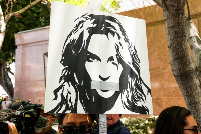 A poster of Britney with duct tape over her mouth held by a supporter at a rally