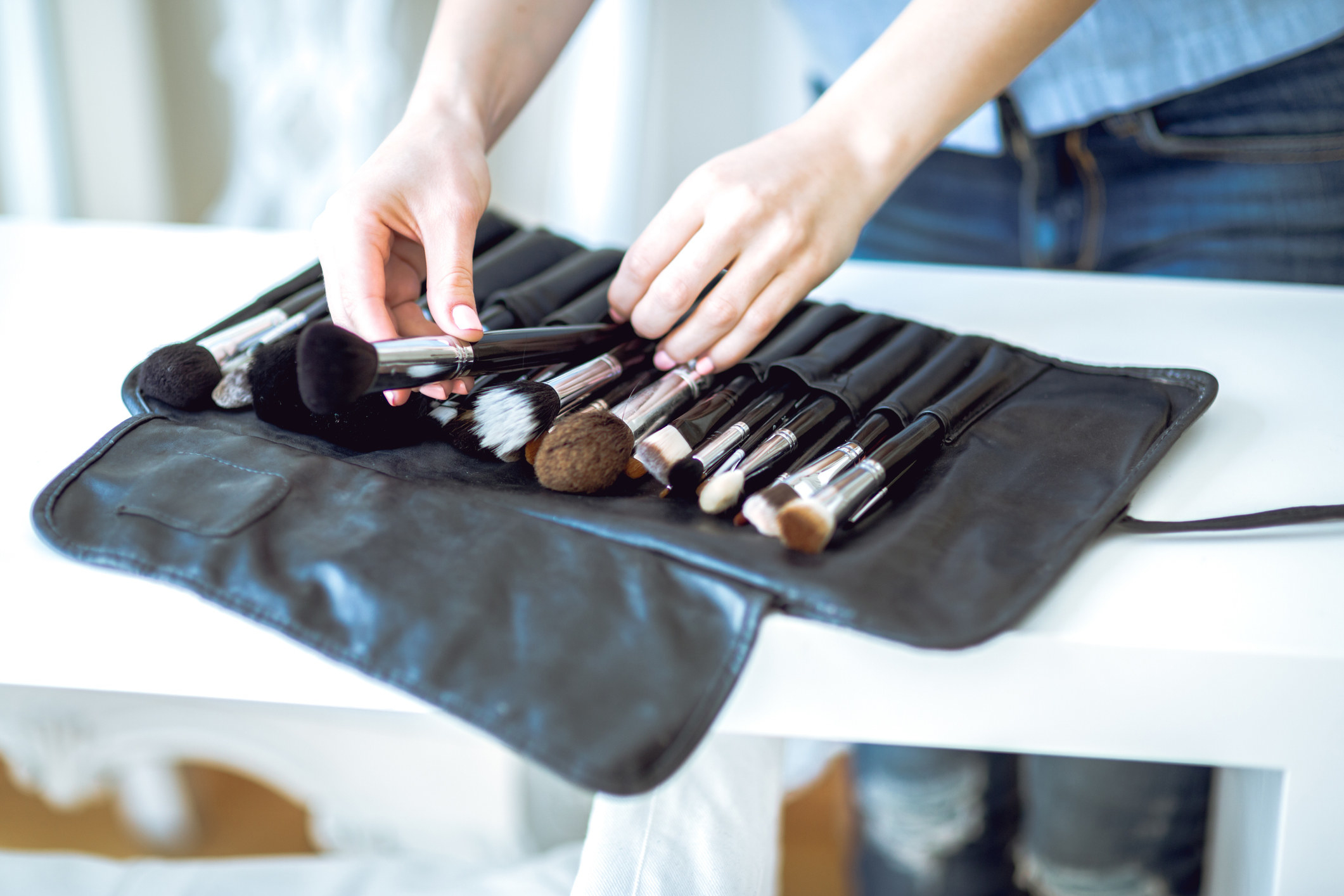 A makeup artist puts some brushes away in their kit