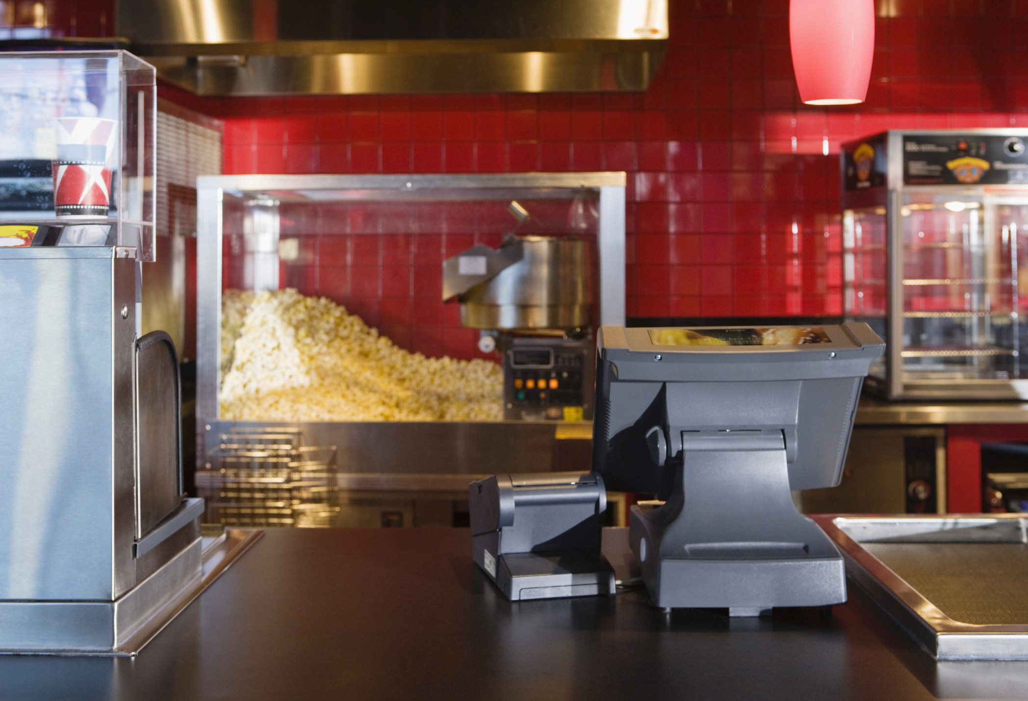 A concession stand at a movie theater, with a popcorn machine and a drink machine