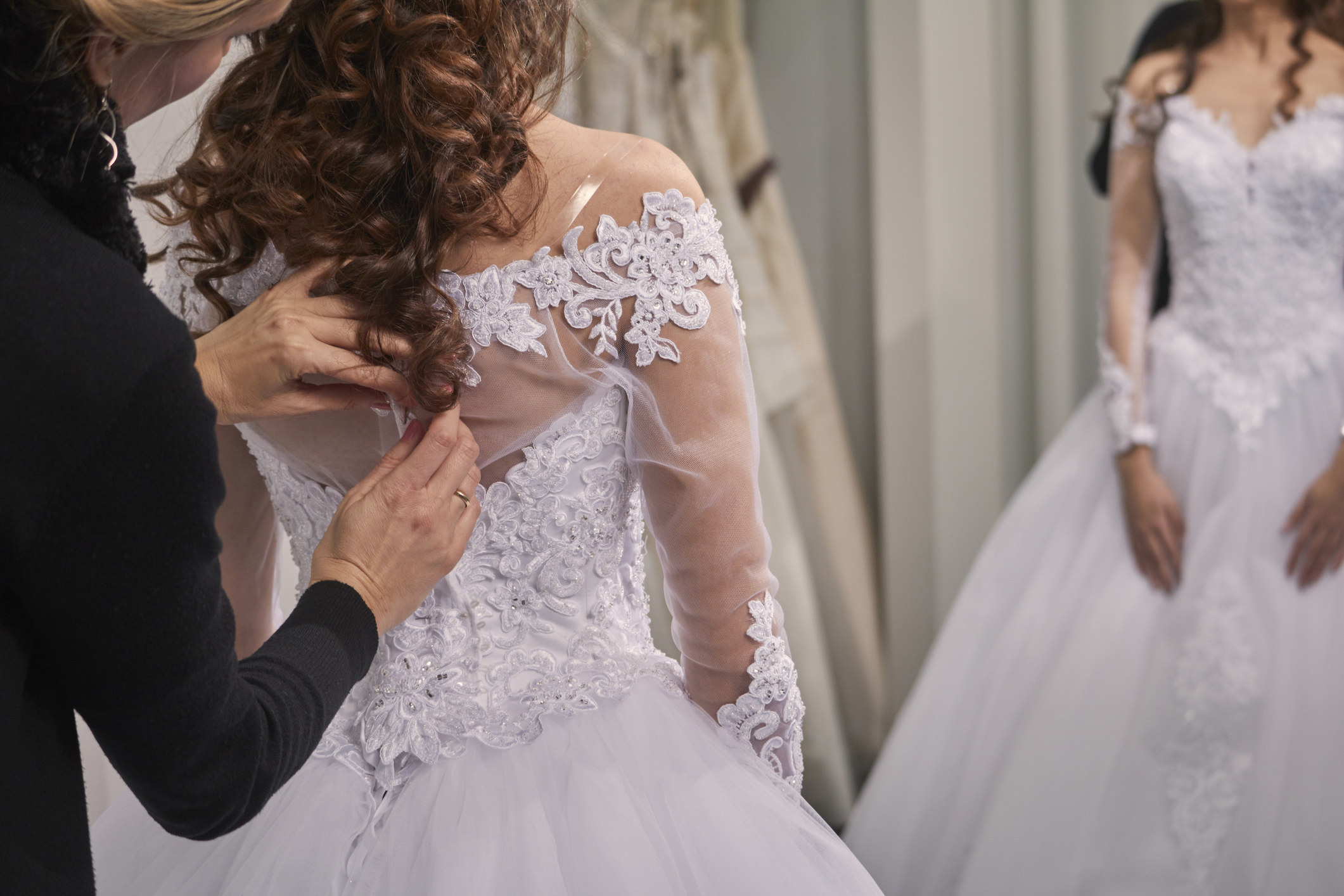 A bride tries on a wedding dress at a store