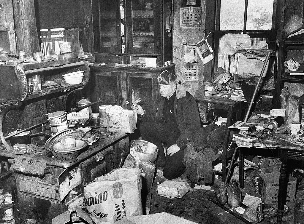 A police officer searching the messy living room of Ed Gein