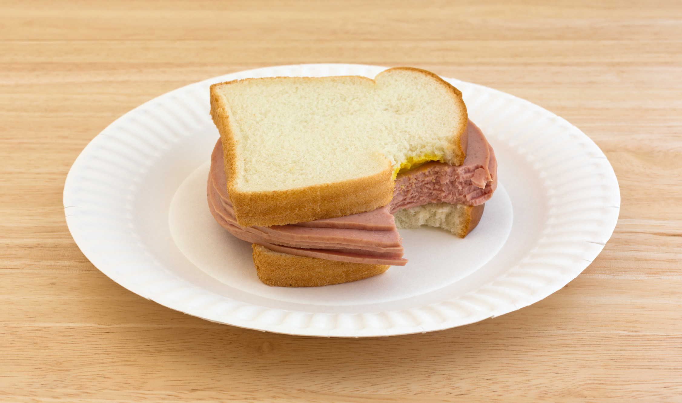 A bologna sandwich on a paper plate
