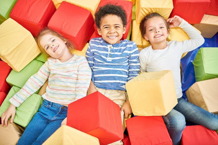 Kids happily play in a foam pit