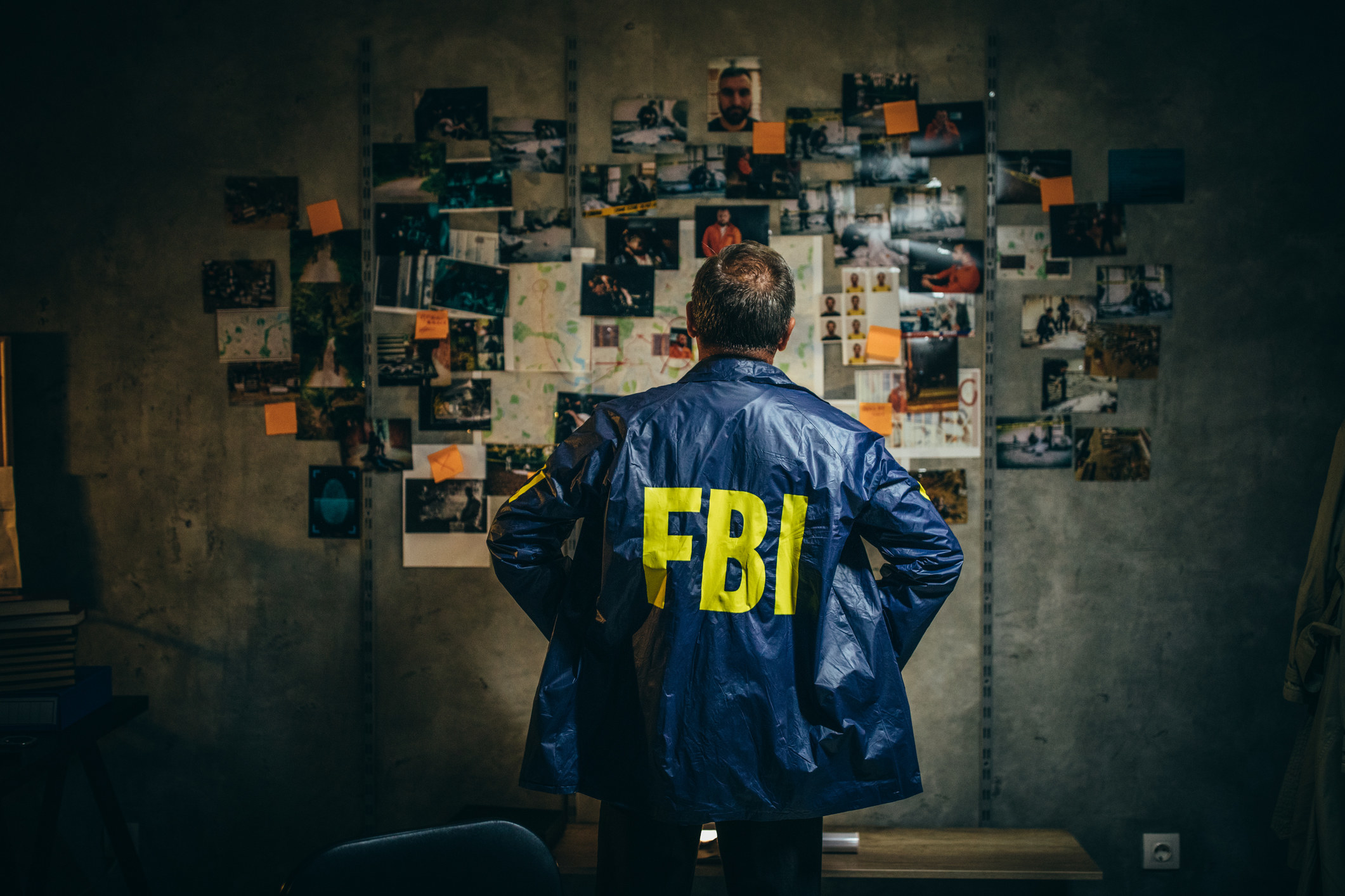 A stock image of an FBI agent looking at a crime board