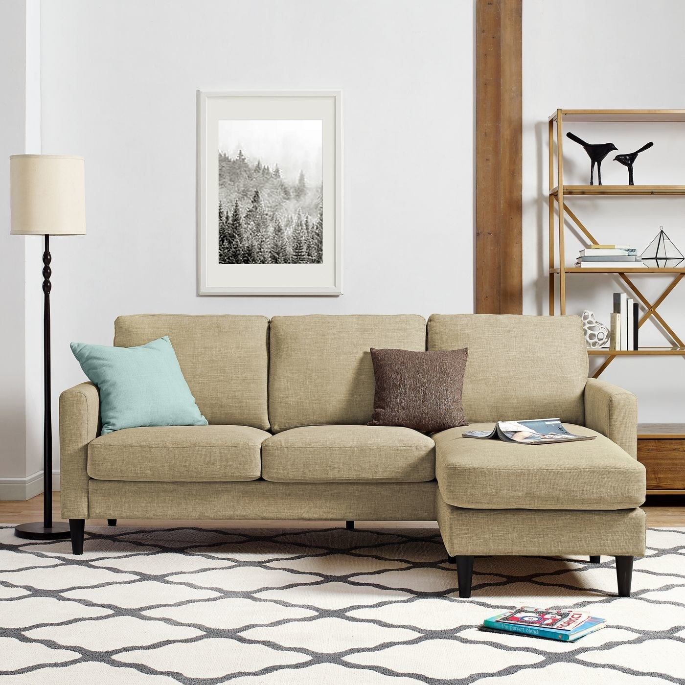 lifestyle photo of the couch in beige with throw pillows and magazine on the chaise