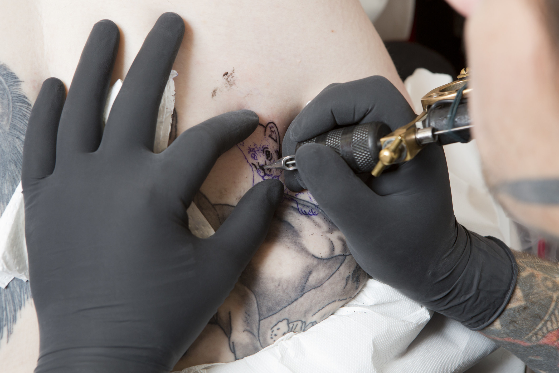 A stock image of a tattoo artist giving someone a tattoo