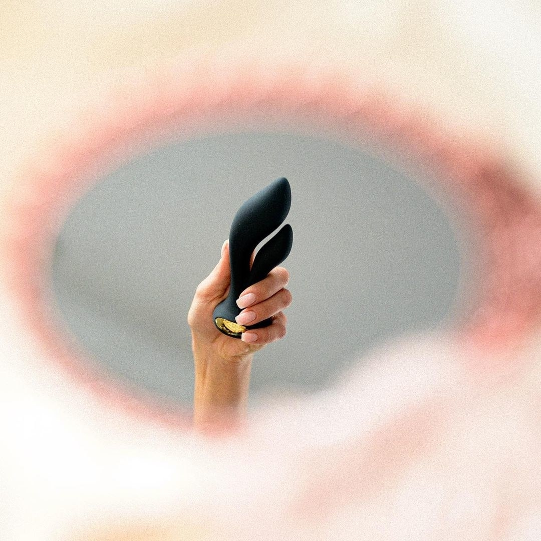 image of a model's hand holding the black Dea up to a mirror