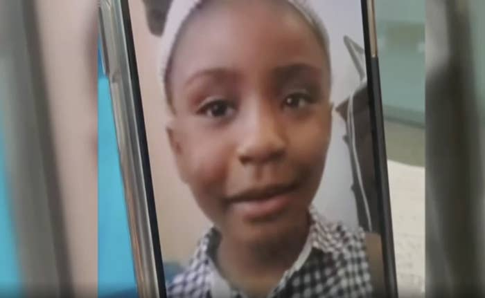 A small Black girl in a gingham top on Facetime.