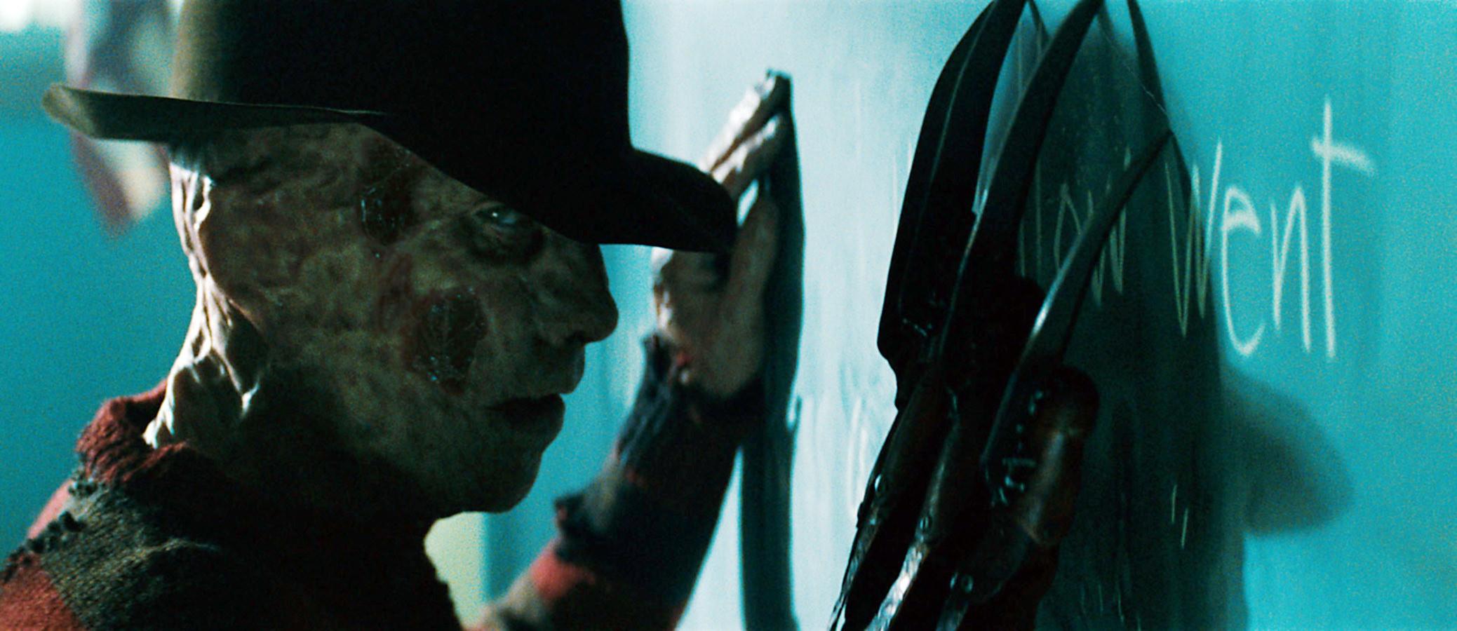 Freddie Krueger in the film against a chalkboard