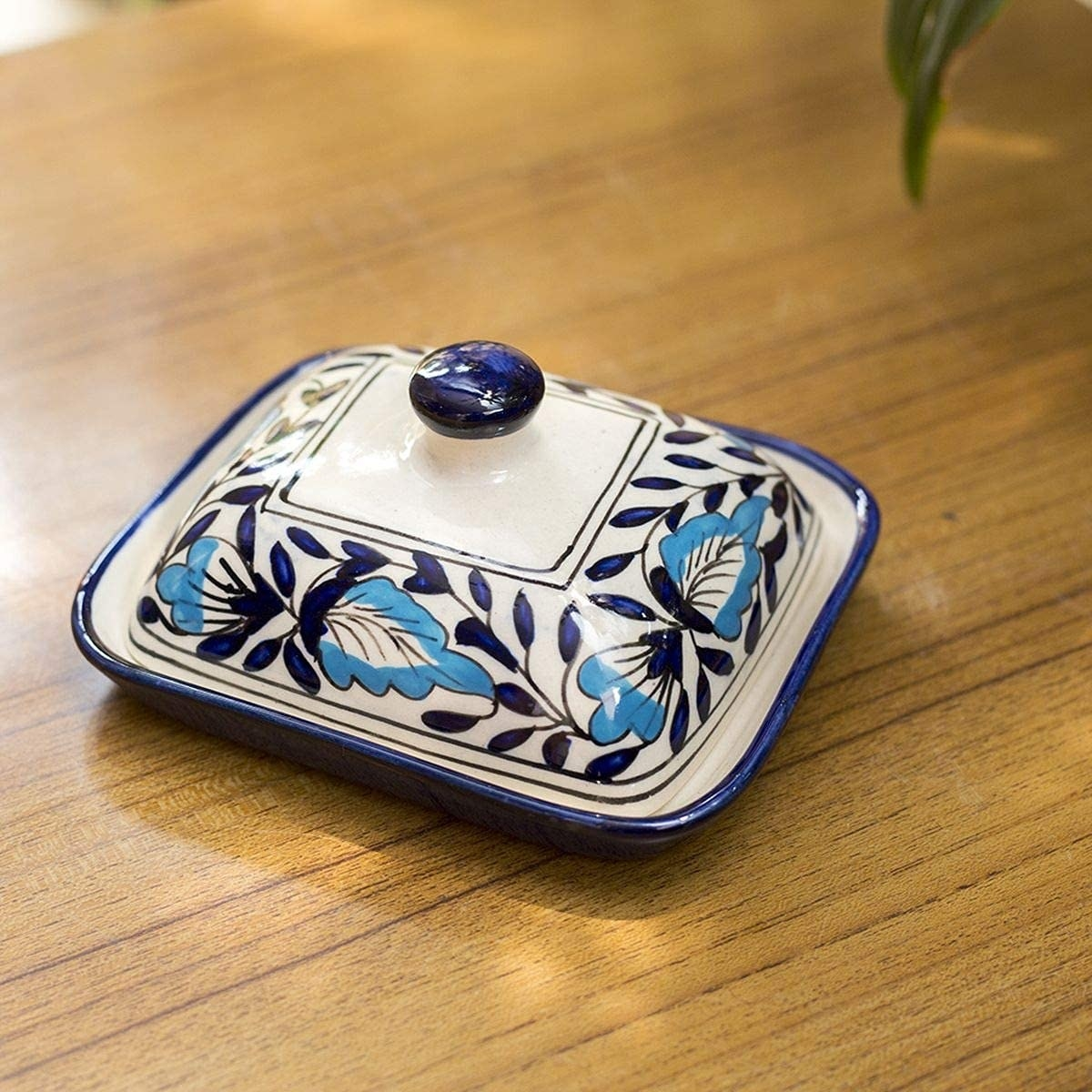 A ceramic butter dish with a blue pottery lid.
