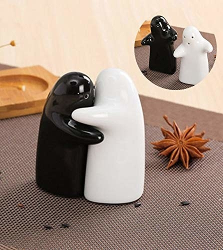 A white and black ghost-shaped set of salt and pepper shaker that are hugging each other.