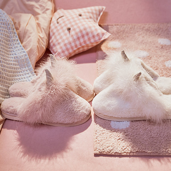 the pink fuzzy slippers with unicorn horns on them
