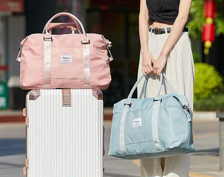 a model holding the blue duffel bag